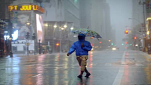 A man walks across 42nd Street in Times Square in New York August 28, 2011 as Hurricane Irene hits the city and Tri State area with rain and high winds.
