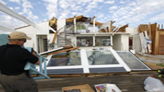 Man clears out belongings from storm-damaged beach home in the Sandbridge area of Virginia Beach, Virginia.