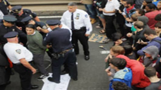 Police arrest demonstrators affiliated with the Occupy Wall Street movement after they attempted to cross the Brooklyn Bridge on the motorway on October 1, 2011 in New York City.