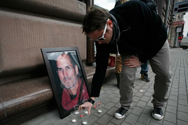 A visitor places a memorial candle beside a photograph of Steve Jobs outside a re:Store, an Apple Inc. product retailer, in Moscow, Russia, on Thursday, Oct. 6, 2011