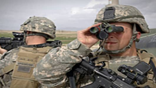 U.S. Army Sgt. Joseph Evans scans the area through a pair of binoculars while Spc. Brendon Quisenberry pulls rear security during a security halt on a route reconnaissance mission near Mir-e, Afghanistan.