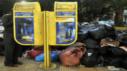 A man makes a phone call next garbage in Athens due to a strike by municipal and public sector workers.