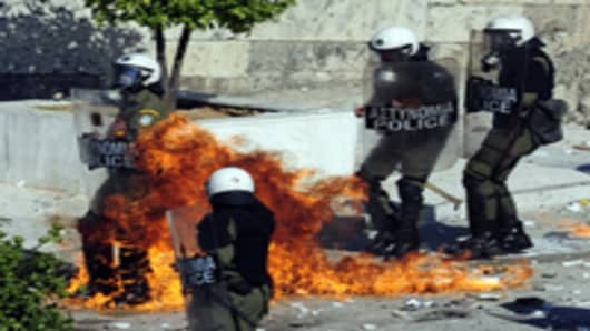 Protesters throw petrol bombs to riot police as they demonstrate in front of the Greek parliament in Athens on October 19, 2011 as a two-day general strike began against a new austerity bill demanded by Greece's international creditors to avert bankruptcy.