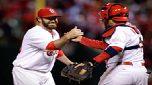 Jason Motte #30 and Yadier Molina #4 of the St. Louis Cardinals celebrate after defeating the Texas Rangers 3-2 during Game One of the MLB World Series at Busch Stadium on October 19, 2011 in St Louis, Missouri.