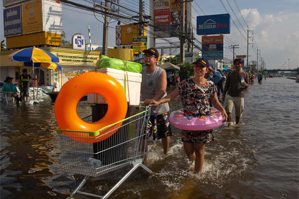 Thai residents stocked up on supplies walking down the flooded streets in Bangyai on the outskirts of Bangkok.