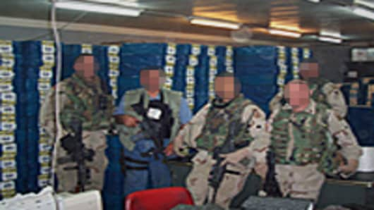 US military officers in front of billions of dollars in cash inside the vault of the Central Bank of Iraq.