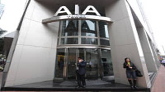 This file photo taken on March 1, 2010 shows people standing near the entrance of the AIA tower in Hong Kong. US insurer AIG said its Asian unit AIA would likely book an annual operating profit of at least two billion USD as the subsidiary prepares to list in Hong Kong, it was reported on September 27, 2010.