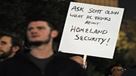 A protester holds up a sign referencing Scott Olsen, 24, a former Marine who has shot in the head by a police projectile during a protest last night.