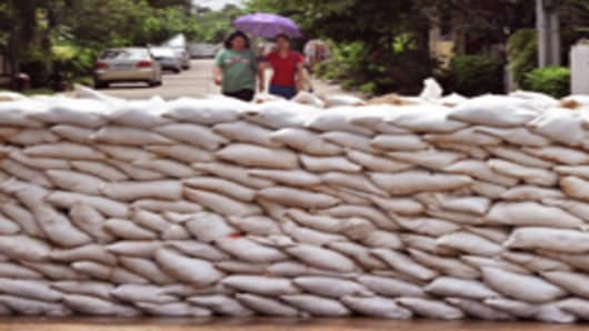 Thai residents walk behind a wall of sandbags piled high to block off floodwaters in Nonthaburi province, suburban Bangkok.