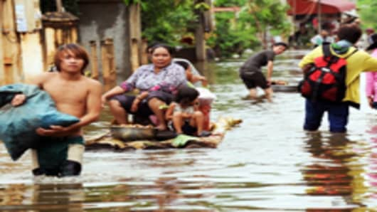 Cambodians use boats to navigate flooded streets at Kian Svay district in Kandal province, 20 kilometers east of Phnom Penh.