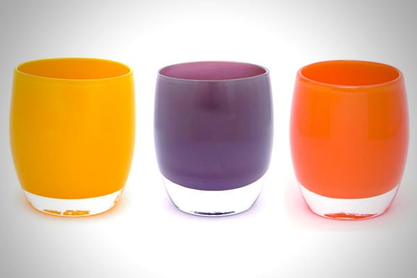 """Whether they're holding wine, a fresh bloom, or a flickering votive, add beauty. Tougher than they look, the multipurpose glasses are made with three layers of glass and glow in a rainbow of colors. Started in 1998 by Lee Rhodes — who was then juggling the care of three young kids while fighting a rare form of lung cancer — Glassybaby supported her search """"for a few moments of serenity."""" The company's built-in goodwill policy has already donated more than half a million dollars to charities that"""