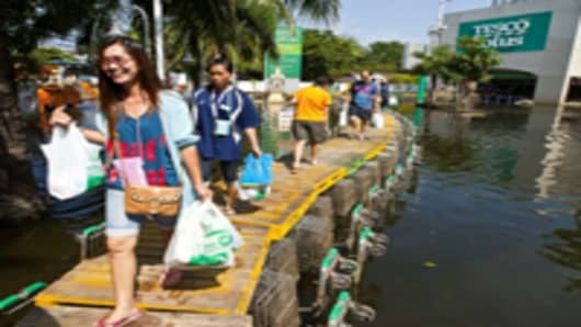 Residents walk on an elevated walkway that uses shopping center caddies flooded north-west Bangkok.