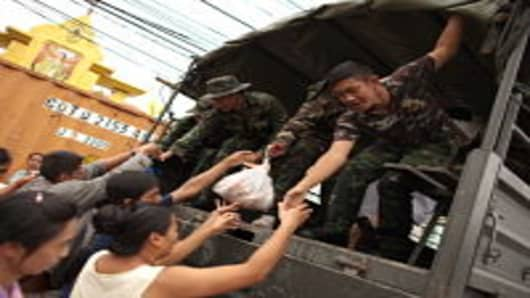 PATUM THANI, THAILAND - OCTOBER 14: Thai soldiers help residents onto a military truck as floods continue to hit Pathum Thani province on October 14, 2011 in Pathum Thani, north of Bangkok,Thailand. Crews of public workers, soldiers and volunteers are evacuating residents from flooded areas north of Bangkok as efforts continue to protect the capital from increased rainfall and rising tides during the worst floods to hit the country for decades.