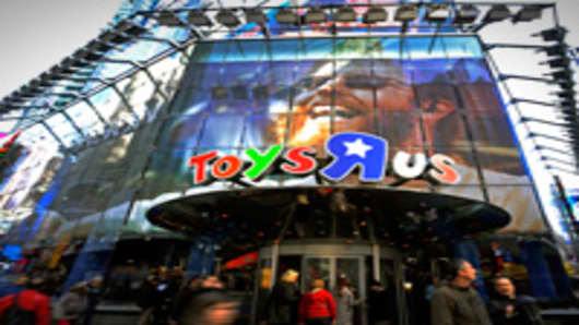 Pedestrians pass in front of a Toy 'R' Us Inc. store in New York.