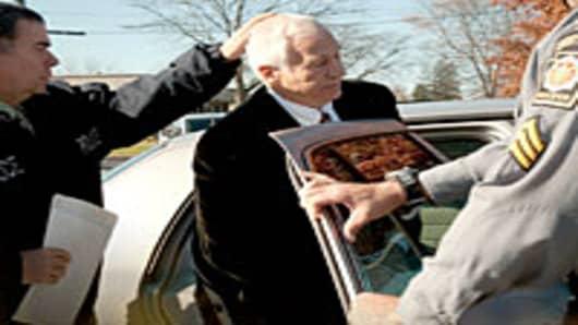 Jerry Sandusky, former Penn State football defensive coordinator (center), placed in police car.