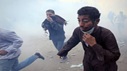 Egyptian protesters run for cover on the third day of clashes with security forces at Tahrir Square in Cairo on November 21, 2011.