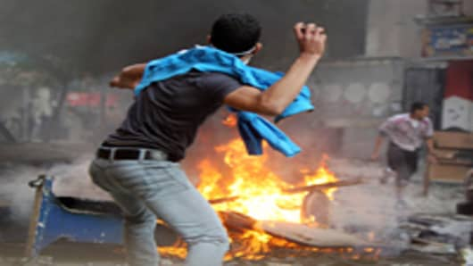 An Egyptian protester throws a stone on the third day of clashes with security forces at Tahrir Square in Cairo on November 21, 2011.