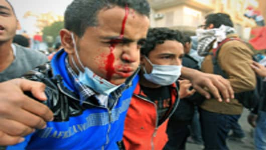 An injured Egyptian protester is helped away during clashes with security forces on the third day at Tahrir Square in Cairo on November 21, 2011.