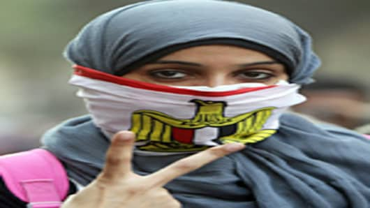 An Egyptian female protester covers her face with the national flag during clashes on the third day with security forces at Tahrir Square in Cairo on November 21, 2011