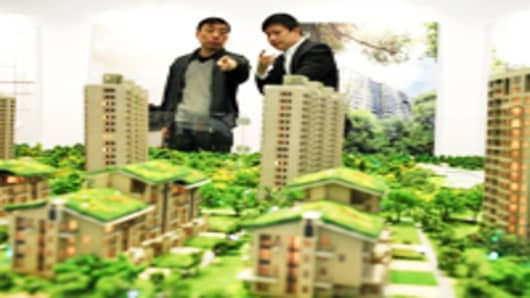 A potential buyer speaks with a real estate agent at a residential property fair in Shanghai, China.