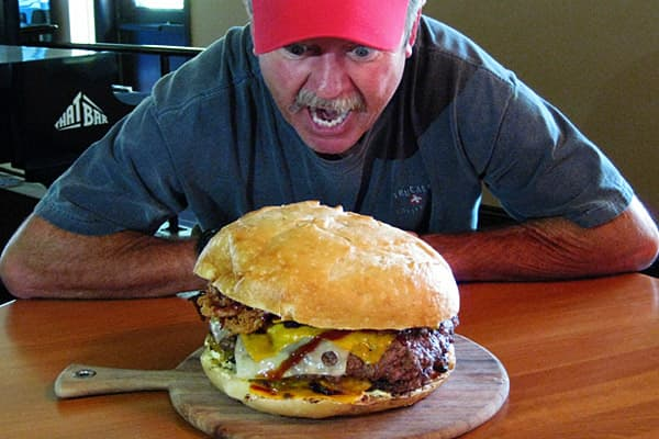 """Restaurant: That Bar Location: Danville, Calif. A massive, undefeated burger challenge can be found at Appropriately named """"That Burger,"""" the monstrous mass of meat and cheese measures approximately 1 foot in diameter, and includes two 100 percent Angus beef patties, one of which has a hole in the middle where a grilled cheese sandwich is placed.  patty is topped with four different cheeses - cheddar, American, pepper jack and Swiss - as well as a woven bacon patty. Finally, the burger is topped"""