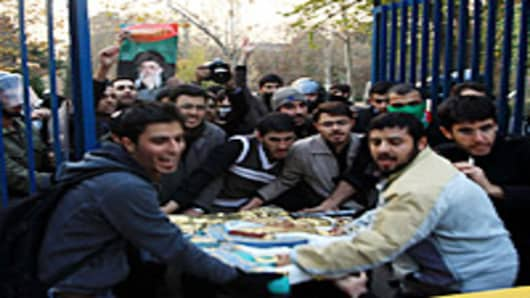 Protesters carry the royal coat of arms after breaking in to the British Embassy during an anti-British demonstration in the Iranian capital on November 29, 2011 in Tehran, Iran.