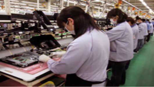 Employees assemble parts for Fujitsu