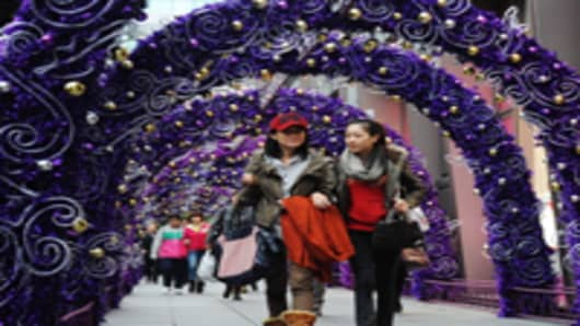 Pedestrians walk through a Christmas decoration at West Nanjing Road in Shanghai, China.