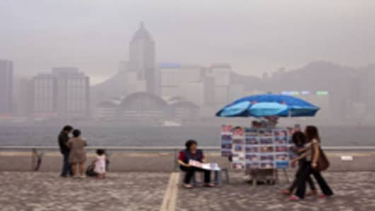 High rise buildings are seen through haze as tourists stroll along the waterfront in Hong Kong, China.