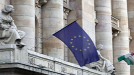 A European Union, left, and a Hungarian national flag, fly outside the Magyar Nemzeti Bank, Hungary's central bank, in Budapest.
