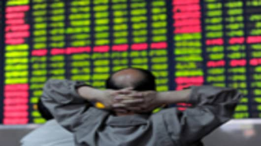 A Chinese investor checks share prices at a security firm in Hefei, east China's Anhui province.