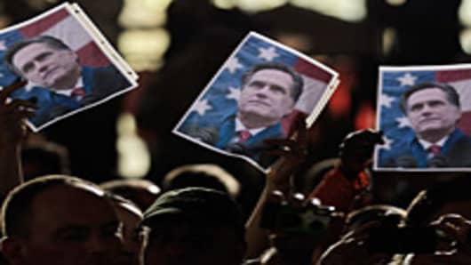 People hold up photographs of Republican presidential candidate, former Massachusetts Gov. Mitt Romney during a campaign rally at a grassroots rally at Winthrop University on January 18, 2012 in Rock Hill, South Carolina