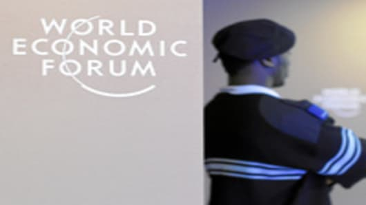 Impression of a security staff next to the WEF-logo during preparation for the upcoming Annual Meeting 2012 of the World Economic Forum in Davos, Switzerland, January 23, 2012.