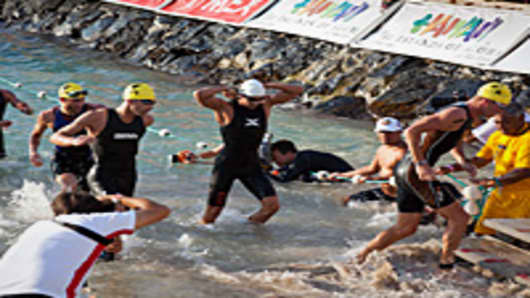 Luke Bell, leads triathletes exiting water after the 2.4 mile swim portion of the Ford Ironman World Championship on October 8, 2011 in Kailua-Kona, Hawaii.