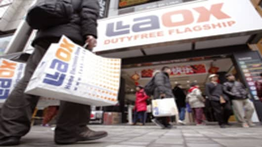 Chinese tourists stand outside a Laox Co. electronics store after shopping in the Akihabara district of Tokyo, Japan, during the Lunar New Year holidays.