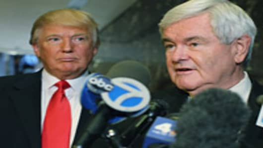 Republican presidential candidate Newt Gingrich speaks to the media as Donald Trump listens at Trump Tower following a meeting between the two on December 5, 2011 in New York City.