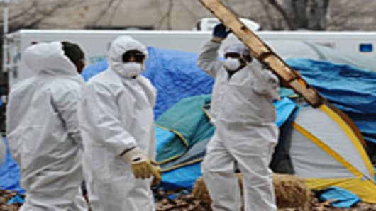 Workers in protective overalls remove items from the Occupy DC encampment in McPherson Square on February 4, 2012 in Washington, DC.