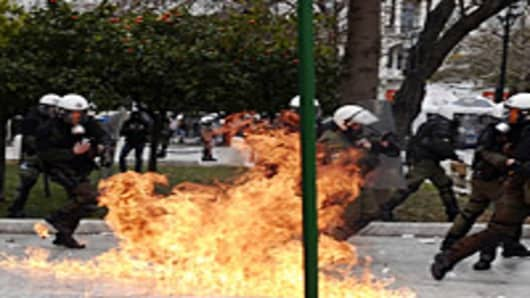 Greek protesters threw stones and firebombs at riot police who responded with tear gas in Athens on February 10 as clashes erupted on the sidelines of a protest against new austerity cuts.