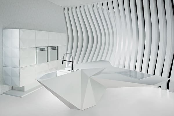 "Who says a kitchen island must be monolithic rectangle topped with a slab of stone? Certainly not the industrial designer Karim Rashid, who designed this for Amr Helmy Designs. The sculptural multi-purpose island features asymmetrical triangular Glacier White Corian surfaces styled to look like a folded paper object. The Origami Island debuted in 2011 as a companion to the Origami Kitchen Rashid designed for the Egyptian kitchen company, whose tagline is ""7 years ahead."""