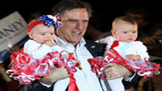 Republican presidential candidate, former Massachusetts Gov. Mitt Romney (L) holds two babies during a campaign rally at West Hills Elementary School March 4, 2012 in Knoxville, Tennessee.
