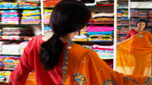 Woman selecting sari in sari shop.