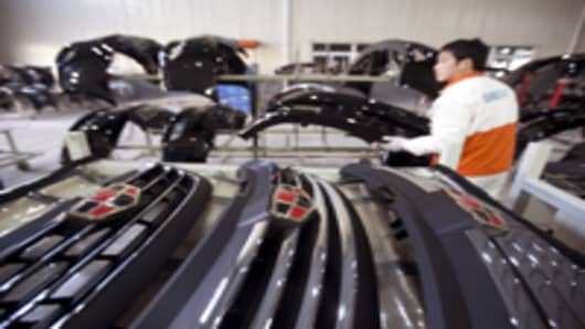 An employee stacks grills for Geely Automobile Holdings Ltd. Emgrand 7 series automobiles at the company's factory in Cixi, Zhejiang Province, China.