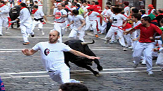 A fighting bull runs behind participants during the San Fermin running of the bulls on July 12, 2011 in Pamplona, Spain.
