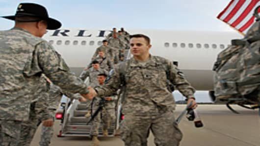 U.S. Army Lieutenant Patrick Mulvaney from Sugar Land, Texas, of the 2-82 Field Artillery, 3rd Brigade, 1st Cavalry Division, is greeted as he walks off the plane as they arrive at their home base of Fort Hood, Texas after being part of one of the last American combat units to exit from Iraq on December 16, 2011 in Fort Hood, Texas.