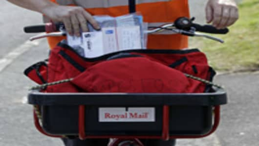 A Royal Mail postal worker, delivers mail on his round in London, U.K., on Monday, July 4, 2011. to mail centers in Greater London.