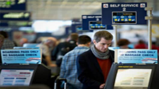 A passenger checks in at an American Airlines Inc. self-service kiosk at O'Hare International Airport in Chicago, Illinois.