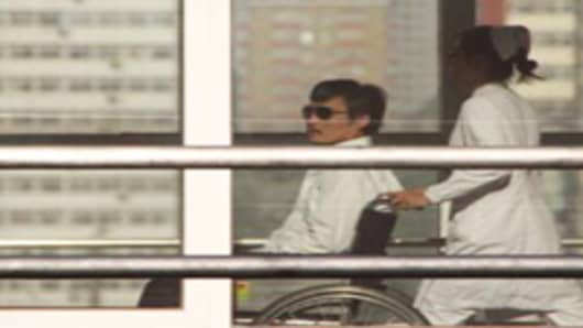 Chinese activist activist Chen Guangcheng is seen in a wheelchair pushed by a nurse at the Chaoyang hospital in Beijing on May 2, 2012.