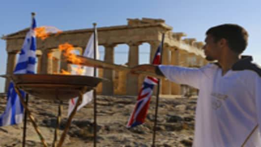 Torchbearer Dimitrios Chondrokoukis, a Greek high jump athlete, lights a cauldron with the Olympic Flame atop the Acropolis in Athens on May 16, 2012. The flame will be handed over to the London olympics officials on May 17.