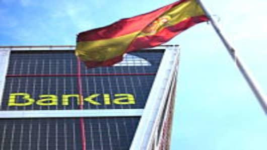 A Spanish national flag flies beneath the Kio towers, the headquarters of Bankia SA in Madrid, Spain.