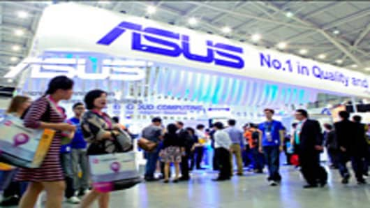 Visitors walk past the Asustek Computer Inc. booth at Computex Taipei 2012 in Taipei, Taiwan, on Tuesday, June 5, 2012.